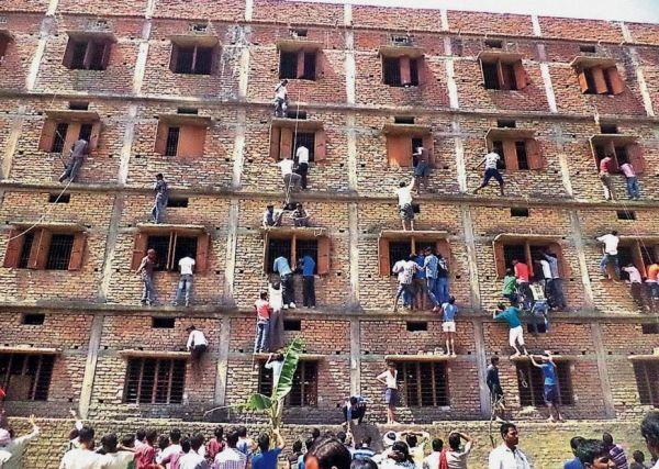 Genitori indiani arrampicati sulle finestre delle scuole